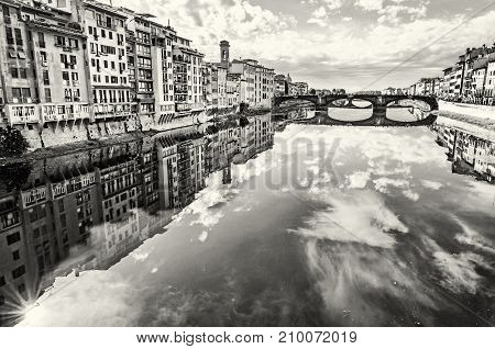 Old buildings and beautiful Ponte Santa Trinita mirrored in the river Arno Florence Tuscany Italy. Travel destination. Black and white photo.