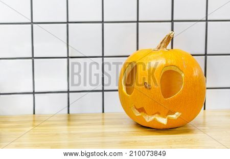 Traditional Halloween Big Orange Pumpkin With Kind Scary Smile And Big Eyes Standing On A Wooden Tab