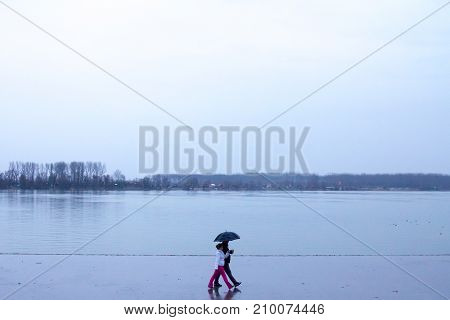 BELGRADE SERBIA - JANUARY 31 2016: People walking with umbrellas near the Danube river during a heavily foggy and rainy winter afternoon in Zemun a northern district of Belgrade