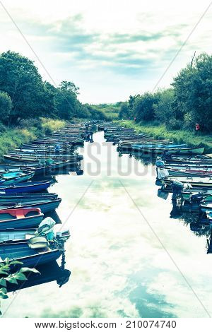KILLARNEY IRELAND - AUGUST 13 2017; Retro styled image boats tied to sides of canal leading to Ross Lake and Ross Castle Killarney Ireland.