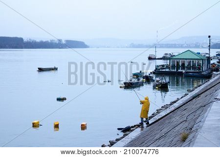 BELGRADE SERBIA - JANUARY 31 2016 Fisherman fishing on the Danube river during a heavily foggy winter afternoon in Zemun a northern district of Belgrade