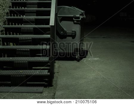 Dark alley with stairs and garbage container