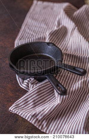 Black Cast-iron Frying Pan With A Towel On A Dark Background