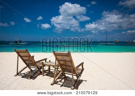 Tropical vacation on white sand beach with sun, blue sky and palm trees. White beach at Boracay island, Philippines.