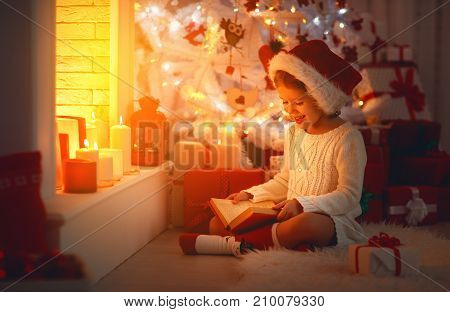 happy child girl read a book at christmas near fireplace at home