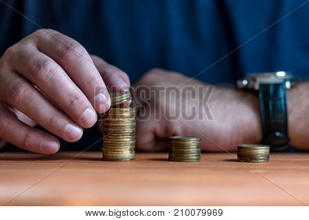 Man stacking money as concept for success or savings, investment and accounting