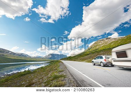 Car with RV trailer in mountains of Norway Europe. Auto travel through scandinavia. Blue cloudy sky and lake in background.