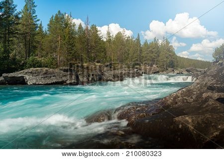 Fast river running through green forest in Norway Europe. Blue sky with clouds in background.