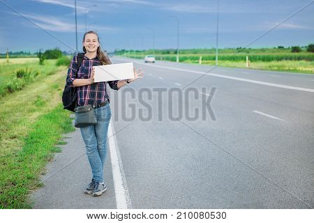 Smiling woman hitchhiker on the road is holding a blank board. Concept: to travel the world, euros, holidays, people, vacations.