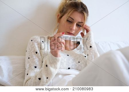 Woman Measuring Her Temperature Lying On The Bed