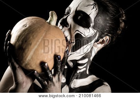 Attractive Girl With Skeleton Makeup Holds A Pumpkin