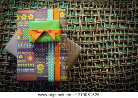 Vintage paper wrapped gifts on woven mat with green background aligned left horizontal aspect