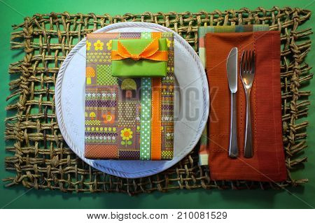 Bright birthday gift boxes in vintage wrapping paper on a white plate with plaid and rust colored napkins on a heavy woven mat