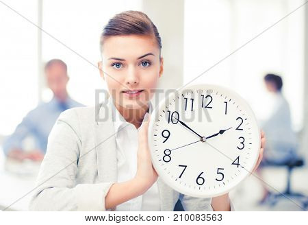 attractive businesswoman showing white clock in office