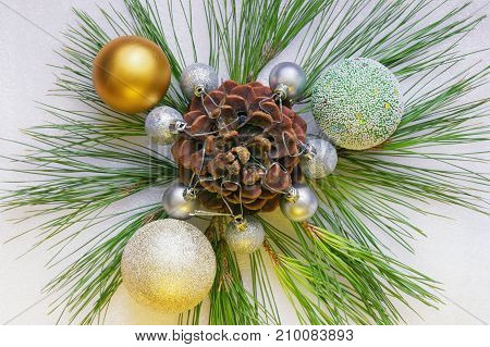 Christmas ornament from pine sprigs cone and Christmas balls