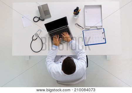 medicine, healthcare and people concept - doctor with cardiogram on clipboard typing on laptop computer sitting at table in clinic