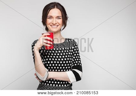 Picture Of Attractive Woman In Speckled Clothes Standing With Cup In Hands