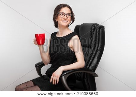 Picture Of Beautiful Woman In Black Dress Sitting In The Armchair With Coffe In Hands