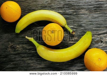 fruit platter of resh mandarins and bananas on gray wooden table view from above