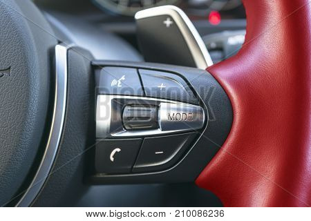 Hands free and media control buttons on the red steering wheel in black leather modern car interior buttons on the steering wheel modern car interior details