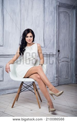 Portrait of attractive young woman sitting in a chair. elegant white dress. White floor and white wall in the background.