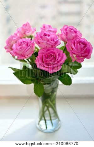 Bouquet of pink roses in glass vase near the window