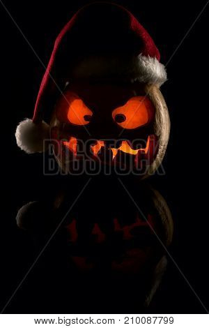 The Concept Of Halloween And The New Year And Christmas. The Evil Scary Pumpkin Santa In The Santa C