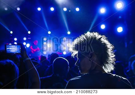 silhouettes of concert crowd and mohawk punk hair style in front of bright stage lights