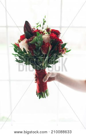 Bride hold wedding bouquet elegance window background