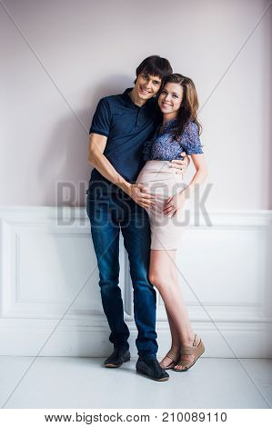 Man kissing his pregnant wife and touching her belly.