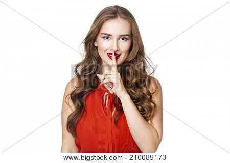 Woman requires silence. Young beautiful blonde woman has put forefinger to lips as sign of silence, isolated on white