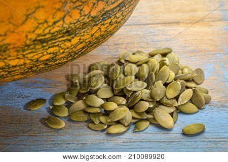 a pile of raw, shelled pumpkin seeds with fresh pumpkin in background