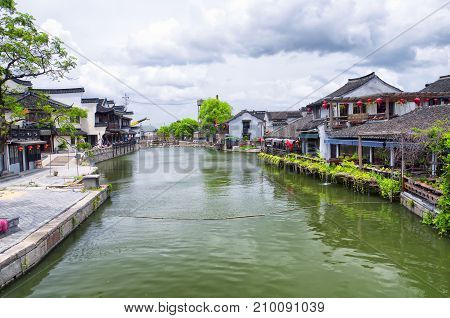 Chinese style buildings surrounding the water canals of Xitang town in Jiashan county in Zhejiang province China. Chinse character fu meaning good luck on a sign.