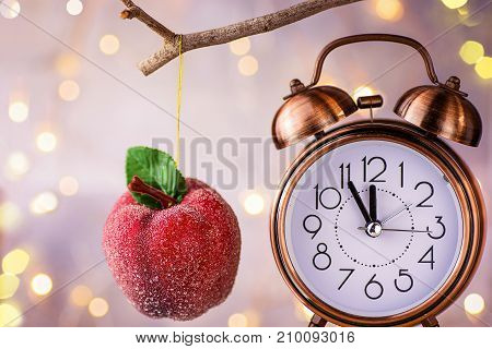 Vintage copper alarm clock showing five minutes to midnight. New Year countdown. Sugar coated red apple ornament hanging on branch. Glittering garland lights. Pastel Colors. Christmas greeting card