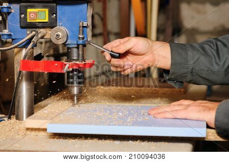 worker hands using wood milling cutter machine on laminated chipboard