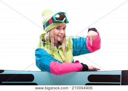 Pretty Young Blonde Woman In Colorful Snow Suit Sitting Cross-legged Behind Snowboard