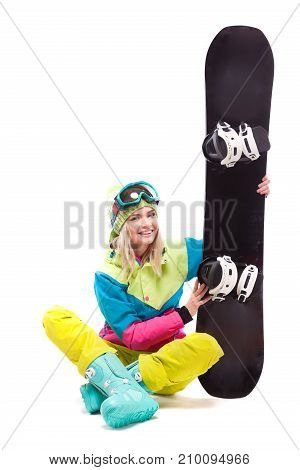 Pretty Young Blonde Woman In Colorful Snow Suit Sitting Cross-legged