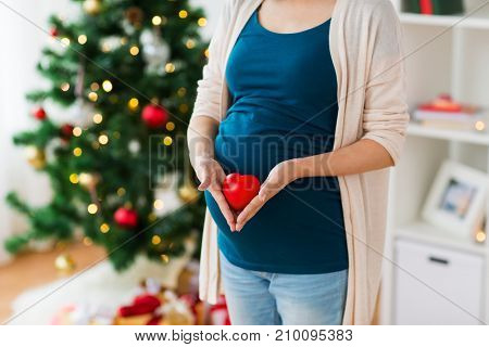 pregnancy, christmas and people concept - close up of pregnant woman with red heart on belly at home