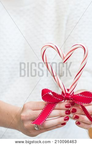 Woman holding Merry Christmas Candy Canes and a red bow in a white sweater in front of a rustic background with room for copy