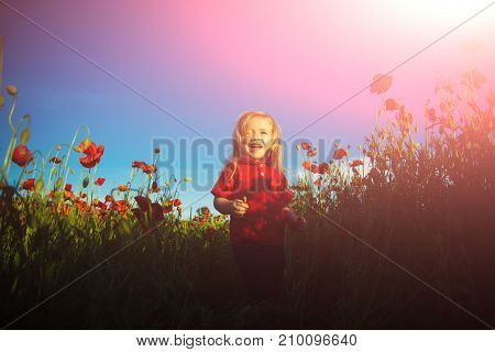 Happy Childhood. Cute Child In Field With Red Poppies. Flowers And Children, Joy And Smile Against T