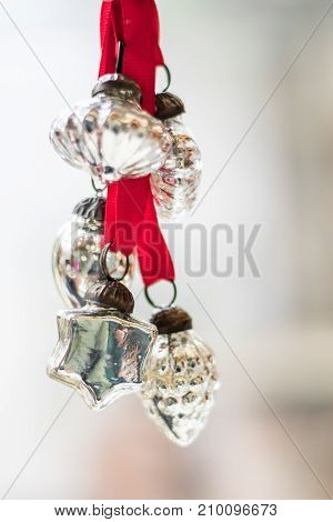 portrait orientation room for copy vintage silver Christmas holiday ornaments on red ribbons hanging in front of a window ready for the Christmas tree