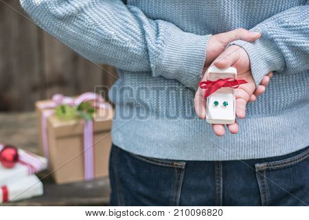 young man holding surprise christmas gifts behind his back in a rustic setting