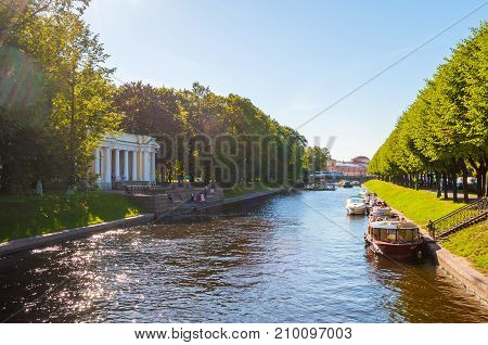 ST PETERSBURG RUSSIA - AUGUST 15 2017. Rossi Pavilion in the Michael Garden and the Moika river with floating pleasure boats in St Petersburg Russia