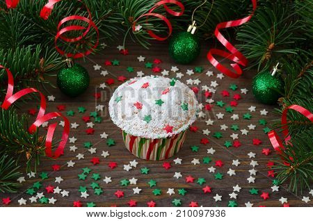 Cupcake with star decoration and christmas tree on wooden background. Christmas and New Year concept