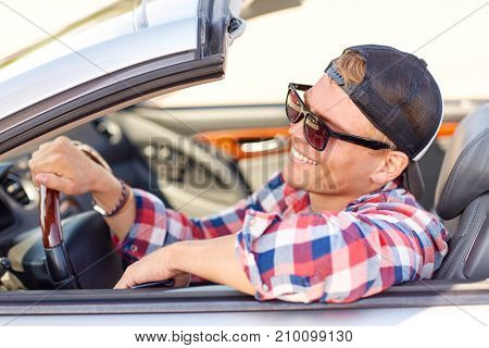 summer holidays, travel, road trip and people concept - happy smiling young man in sunglasses and cap driving convertible car