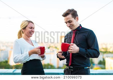 Couple Of Businessmen, Attractive Brunette Man And Pretty Blonde Woman Stand On The Roof And Drink C
