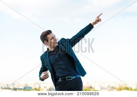 Young Serious Busunessman In Dark Suit, Watch And Black Shirt Stand On The Roof