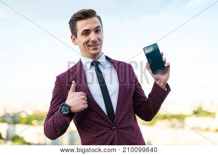Young Serious Businessman In Red Suit And Shirt With Tie Stand On The Roof And Show Empty Phone