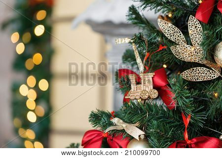 Christmas toy train and garland on the fir tree.