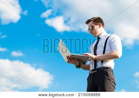 Attractive Serious Busunessman In White Shirt, Tie, Braces And Sunglasses On The Roof With Laptop